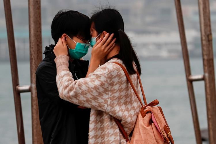 Una pareja con máscaras por el coronavirus se abraza en el día de San Valentín en Hong Kong, China, el 14 de febrero de 2020 (REUTERS/Tyrone Siu)