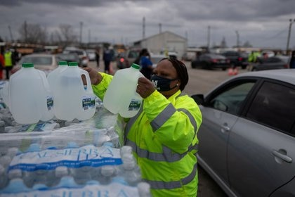 FILE PHOTO: Volunteer Elizabeth Murray helps deliver water at Butler Stadium in Houston, Texas, United States, February 21, 2021. REUTERS / Adrees Latif