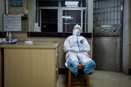 FOTO DE ARCHIVO: Una trabajadora sanitaria en traje de protección toma un descanso durante su turno de noche en un centro de servicios de salud de la comunidad, que tiene una sección aislada para recibir pacientes con síntomas leves causados por el nuevo coronavirus y pacientes sospechosos del virus, en el distrito Qingshan de Wuhan, provincia de Hubei, China, el 9 de febrero de 2020. Foto tomada el 9 de febrero de 2020. China Daily via REUTERS