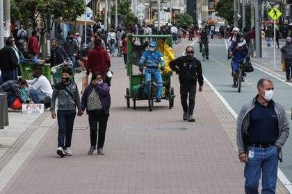 Personas con mascarillas caminan por una calle durante la cuarentena impuesta por el gobierno para reducir las tasas de contagio de COVID-19, en Bogotá, Colombia (REUTERS/Luisa González)