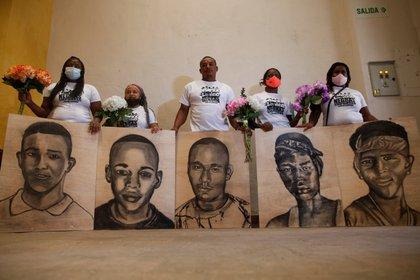 Familiares de las víctimas de la masacre de Llano Verde, sostienen hoy retratos suyos durante un acto conmemorativo, en Cali (Colombia). EFE/ Ernesto Guzmán Jr