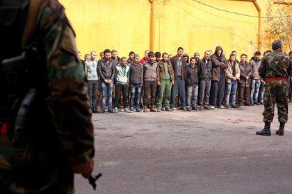 Miembros del Ejército sirio preparan a los civiles para la evacuación de Alepo