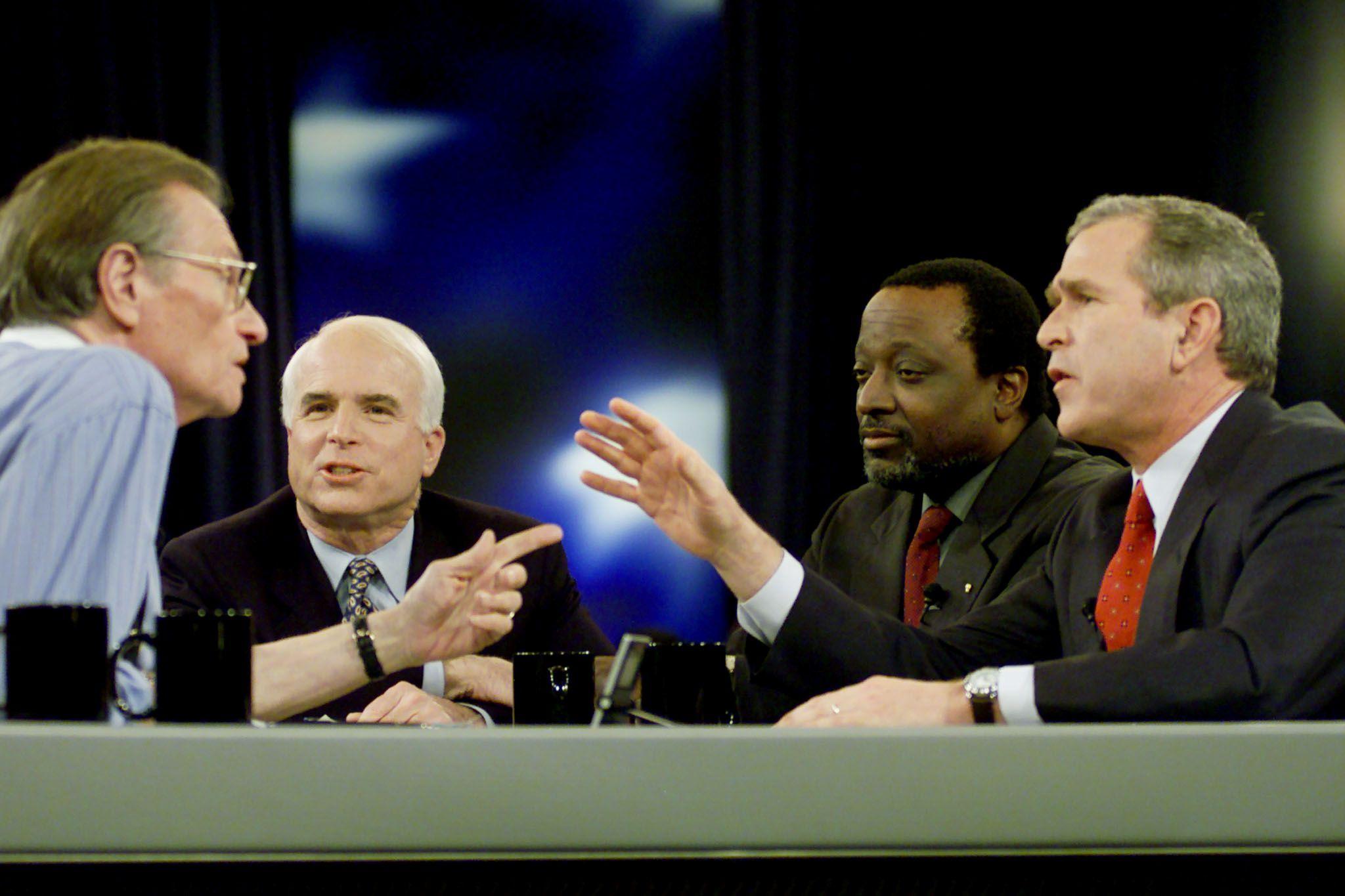 :Los candidatos presidenciales republicanos George W. Bush (R), el presentador Alan Keyes y el senador de Arizona John McCain (2NDL) participan en un debate presidencial republicano televisado por la cadena CNN con el moderador Larry King (L) en Columbia, Estados Unidos, el 15 de febrero de 2000.