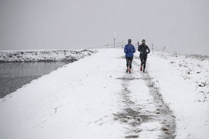 Dos mujeres corren en Brun Clough Reservoir en el pueblo de Delph, cerca de Manchester, Inglaterra. OLI SCARFF / AFP