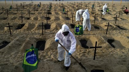 Activists of the NGO Rio de Paz in protective gear dig graves on Copacabana beach to symbolise the dead from the coronavirus disease (COVID-19) during a demonstration in Rio de Janeiro, Brazil, June 11, 2020. REUTERS/Pilar Olivares - RC2Z6H9RJVM6