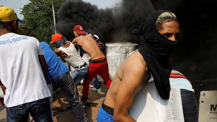 Partidarios de la oposición descargan ayuda humanitaria de un camión que fue incendiado luego de enfrentamientos entre simpatizantes de la oposición y las fuerzas de seguridad de Venezuela(Reuters/ Marco Bello)