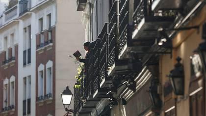 Una mujer lee un libro en un balcón en medio de la cuarentena en Madrid, España. REUTERS/Sergio Perez