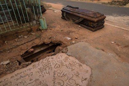 Un ataúd oxidado yace junto a una tumba excavada por ladrones en el cementerio Corazón de Jesús, en Maracaibo, Venezuela, el 21 de noviembre de 2019 (AP)