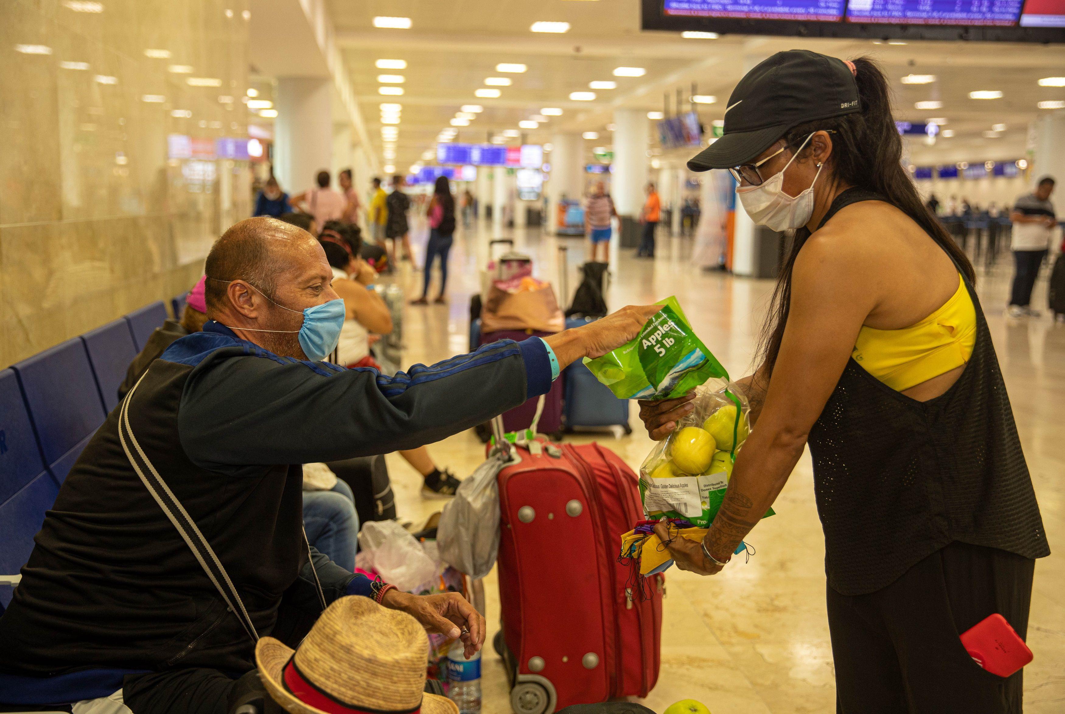 Una mujer regala manzanas a un turista en el aeropuerto internacional de Cancún, en el estado de Quintana Roo (México). (Foto: EFE/Lourdes Cruz)