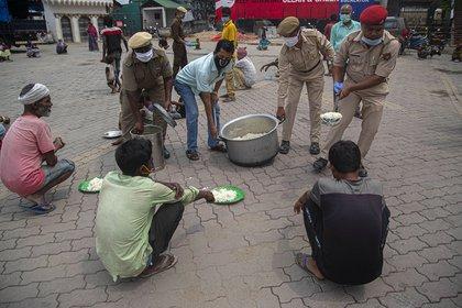 La policía distribuye alimentos gratuitos a las personas sin hogar durante el cierre nacional en Gauhati, India, el jueves 23 de abril de 2020 (AP Photo/Anupam Nath)