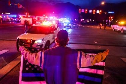 Un hombre sostiene una bandera de línea azul delgada mientras vehículos de emergencia escoltan el cuerpo del oficial de policía asesinado Eric Talley desde la escena del tiroteo en una tienda de comestibles King Soopers en Boulder, Colorado (Reuters)
