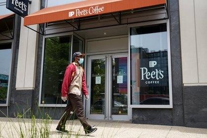 Un hombre camina junto a una tienda cerrada en Washington (Reuters)
