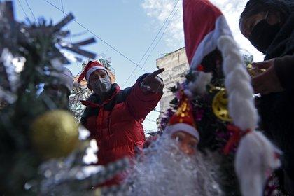 Un hombre disfrazado de Santa Claus en Kathmandu (Photo by Prakash MATHEMA / AFP)