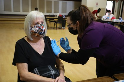 FILE -- A person receives a Pfizer-BioNTech COVID-19 vaccination at the Community Center in Rohnert Park, Calif., on Jan. 27, 2021. Coronavirus vaccines can cause enlarged lymph nodes in the armpit or near the collarbone, which may be mistaken for a sign of cancer. (Jim Wilson/The New York Times)
