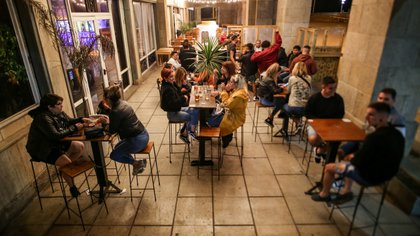 Frente a la rambla de Mar del Plata se respeta el distanciamiento al aire libre entre las mesas de una cervecería