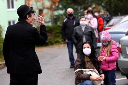 El mimo Vlado Kulisek entretiene a las personas en fila para someterse a una prueba en Trencin, Eslovaquia (REUTERS/Radovan Stoklasa)