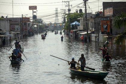 Residentes de Villahermosa utilizan botes para desplazarse por las calles inundadas de la ciudad, tras los estragos causados por el Frente Frío 12 y las bandas nubosas de la tormenta tropical Eta (Foto: AP/Félix Márquez)