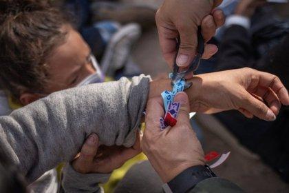 Un agente fronterizo retira un brazalete a un migrante solicitante de asilo, originario de El Salvador (Foto: REUTERS/Adrees Latif)