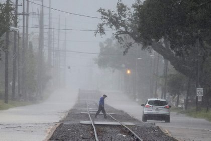 Un hombre regresa a su vehículo después de comprobar las condiciones de la carretera durante las fuertes lluvias antes de la llegada del huracán Delta a Lake Charles, Louisiana, el 9 de octubre de 2020.  REUTERS/Adrees Latif