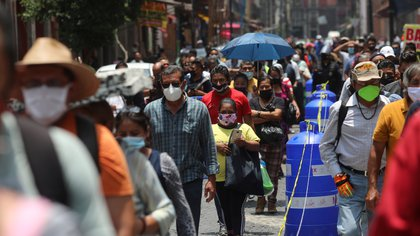 People wait in line along the street before entering the area where stores are open, during the gradual reopening of commercial activities in the city, as the coronavirus disease (COVID-19) outbreak continues, in Mexico City, Mexico July 6, 2020. REUTERS/Henry Romero
