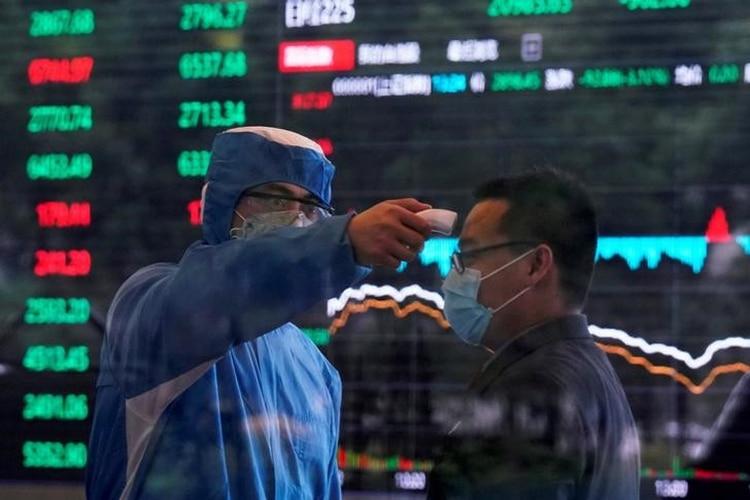 Un trabajador con traje de protección toma la temperatura corporal de una persona en el edificio del Shanghai Stock Exchange, en China.