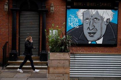 Un graffiti con el rostro del premier Boris Johnson en un bar cerrado por las restricciones (Reuters)