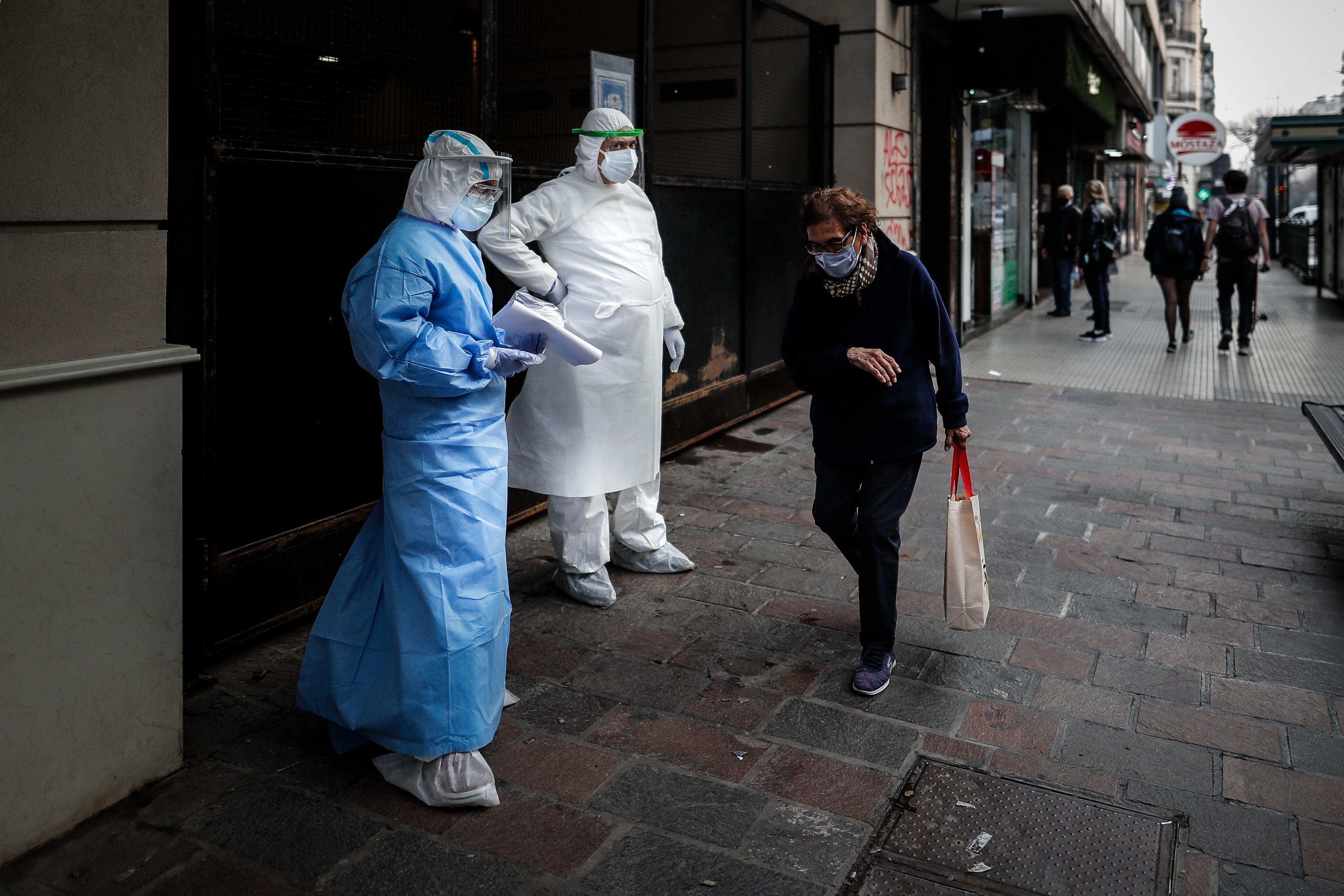 Una mujer pasa frente a personal con trajes de bioseguridad (EFE/Juan Ignacio Roncoroni)