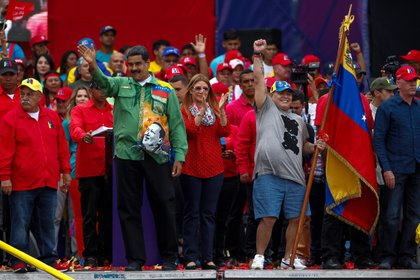 El presidente venezolano, Nicol�s Maduro (i), saluda junto a la primera dama, Cilia Flores (c), y al exfutbolista argentino Diego Maradona (d), durante su evento de cierre de campa�a el 17 de mayo de 2018, en Caracas (Venezuela). EFE/Cristian Hern�ndez/Archivo