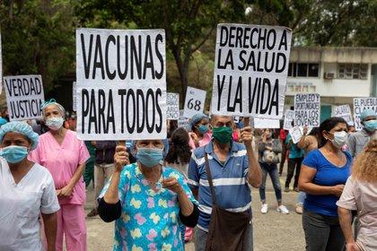 Trabajadores de la salud sostienen carteles durante una manifestación por el Día de los trabajadores en Caracas (EFE/RAYNER PEÑA R./Archivo)