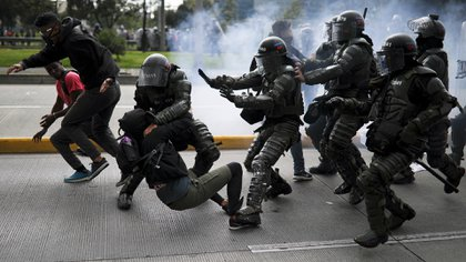 Police detain an anti-government demonstrator during a nationwide strike in Bogota, Colombia, Thursday, Nov. 21, 2019. Colombia's main union groups and student activists called for a strike to protest the economic policies of Colombian President Ivan Duque government and a long list of grievances. (AP Photo/Ivan Valencia)