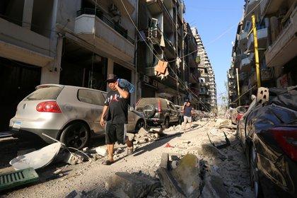 Hombres cargan botellones de agua en una zona muy afectada por la explosión (Reuters)