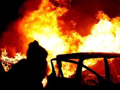 """Un manifestante es visto cerca de un auto en llamas en la puerta del """"muro de la paz"""" en Lanark Way mientras continúan las protestas en Belfast, Irlanda del Norte, 7 de abril de 2021 (REUTERS/Jason Cairnduff)"""