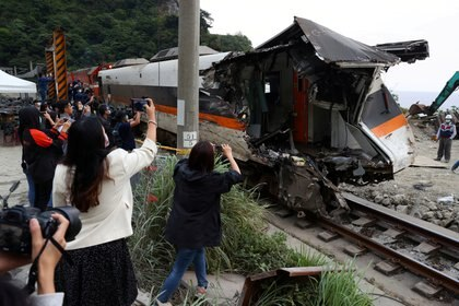 Personas toman fotografías al tren accidentado. REUTERS/Ann Wang     TPX IMAGES OF THE DAY