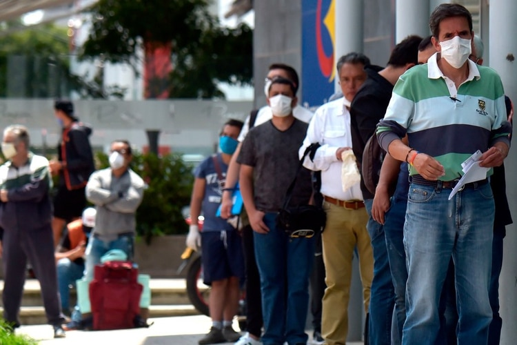 Personas con barbijo hacen fila para ingresar a un comercio en Colombia