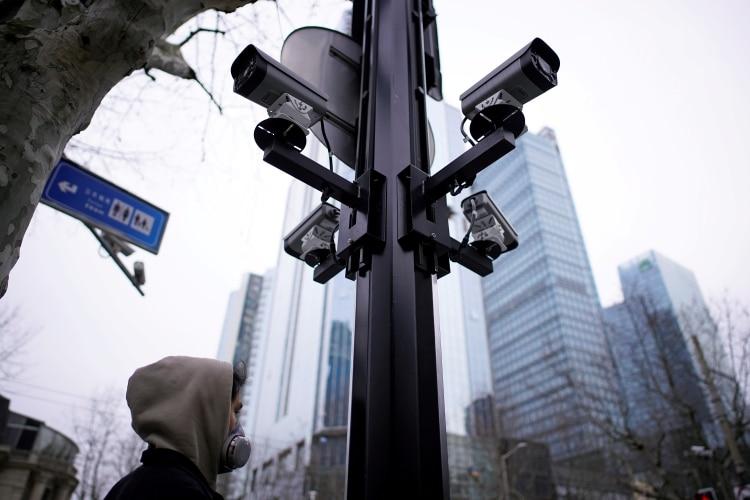 FOTO DE ARCHIVO: Un hombre con una máscara protectora camina bajo cámaras de vigilancia en Shanghai, China, el 4 de marzo de 2020. (REUTERS / Aly Song/archivo)