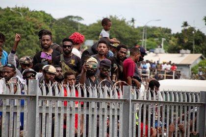 Esta foto tomada el 14 de marzo de 2021 muestra una multitud de personas sin máscaras faciales ni distanciamiento social, reunidas frente al Aeropuerto Internacional Jacksons en Port Moresby para despedirse del ataúd del primer primer ministro de Papúa Nueva Guinea, Michael Somare. (Foto de Andrew KUTAN / AFP)