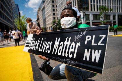 Un hombre sostiene un letrero de la calle Black Lives Matter, en Washington, EE.UU., el 27 de julio de 2020. REUTERS/Al Drago