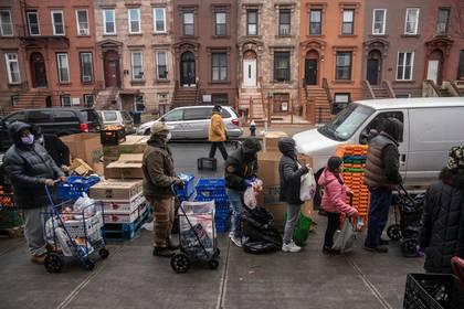 Filas para recibir alimentos gratis en la Open Door Church of God in Christ en Brooklyn el sábado último (Victor J. Blue/The New York Times)