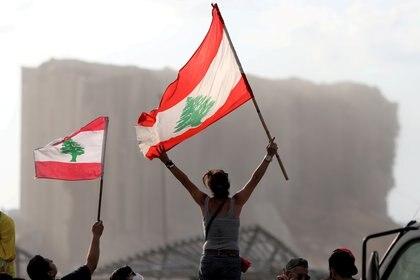 Manifestantes ondean banderas libanesas durante las protestas cerca del lugar de la explosión en la zona portuaria de Beirut, el 11 de agosto de 2020 (REUTERS/Goran Tomasevic/Foto de archivo)
