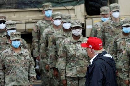 El presidente Donald Trump camina frente a los miembros de la Guardia Nacional que trabajan en las tareas de emergencia provocadas por el Huracán Laura.  REUTERS/Tom Brenner