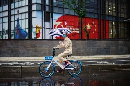 Una mujer con un paraguas monta una bicicleta compartida junto a una imagen de la bandera china después de que se levantó el bloqueo en Wuhan, la capital de la provincia de Hubei y el epicentro de China del nuevo brote de la enfermedad del coronavirus (Reuters)
