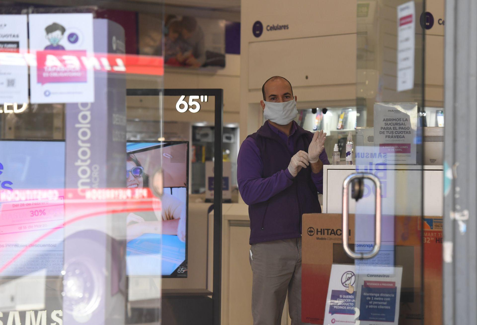 Un empelado de una cadena de retail con guantes y barbijo. Este sector fue otro de los que volvió a la actividad a partir de este martes.