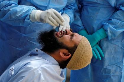 Un hombre gesticula mientras los médicos insertan un hisopo para realizar un test de diagnótico de coronavirus (Reuters)
