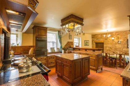 La cocina rústica con alacenas en madera pero con electrodomésticos de última generación (Airbnb)