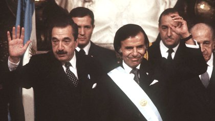 El ex presidente Carlos Menem murió a los 90 años tras permanecer internado en el Sanatorio Los Arcos por dos meses. En la foto, en la ceremonia de traspaso de mando con Raúl Alfonsín. (Foto NA).