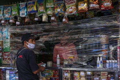 A man shops at a store covered with plastic as a precautionary measure against the spread of the new coronavirus, COVID-19, in Caracas, on March 17, 2020 - President Nicolas Maduro asked the International Monetary Fund on Tuesday for a $5 billion loan to help crisis-worn Venezuela cope with the onslaught of the coronavirus. (Photo by Cristian Hernandez / AFP)