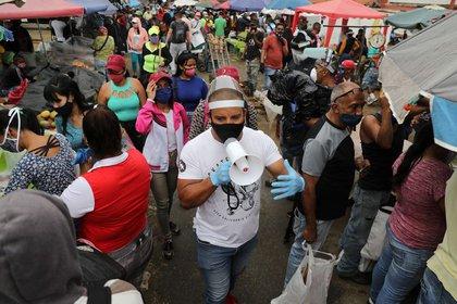 Walter Rivera, director del mercado mayorista Coche, anuncia con un megáfono las reglas para evitar el coronavirus (COVID-19) a locatarios y clientes en Caracas, Venezuela. 23 julio 2020. REUTERS/Manaure Quintero
