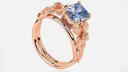 El anillo es de oro rosa, con un diamante azul incrustado y motivos florales
