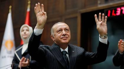 El presidente turco Tayyip Erdogan saluda a los miembros de su partido gobernante AKP durante una reunión en el parlamento en Ankara (Reuters)
