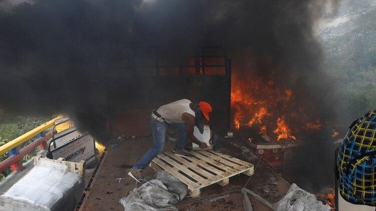Un manifestante rescata la ayuda humanitaria desde un camión incendiado por las fuerzas del régimen de Nicolás Maduro (REUTERS/Marco Bello)